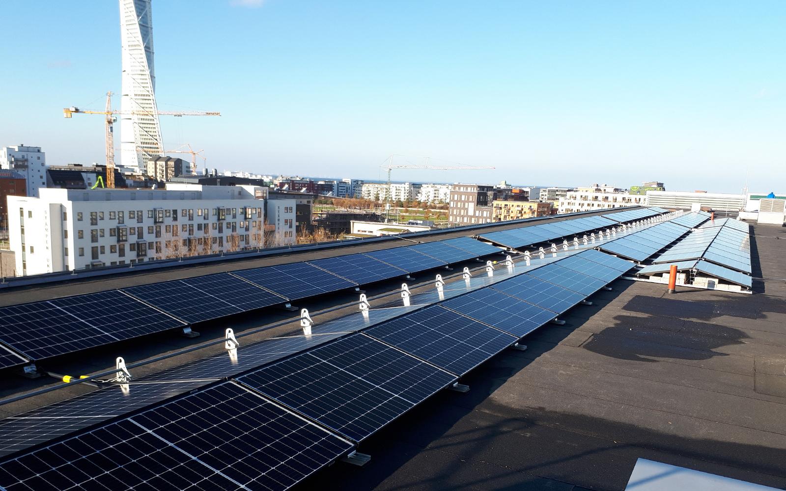 solpaneler på tak med turnning torso i bakgrunden